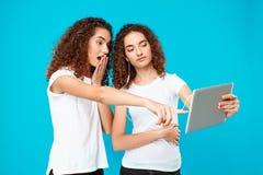 Deux jumeaux de filles regardant le comprimé, étonné au-dessus du fond bleu Images stock