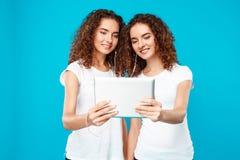 Deux jumeaux de filles regardant le comprimé, souriant au-dessus du fond bleu Photo libre de droits