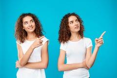 Deux jumeaux de filles souriant, dirigeant des doigts loin au-dessus de fond bleu photographie stock