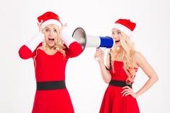Deux jumeaux de soeurs ayant l'amusement avec le mégaphone Photo libre de droits