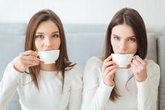 Deux jumeaux de soeurs s'asseyant sur le sofa et le café potable Image stock