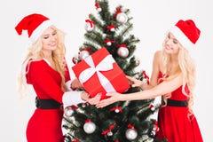 Deux jumeaux de soeurs tenant un cadeau près de l'arbre de Noël Image libre de droits
