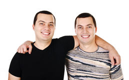 Deux jumeaux de sourire positifs attirants de jeunes hommes d'isolement Images stock