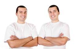 Deux jumeaux de sourire positifs attirants de jeunes hommes d'isolement Photographie stock