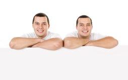 Deux jumeaux de sourire positifs attirants de jeunes hommes d'isolement Image stock