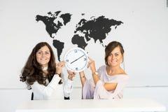 Deux jumelles de jeunes filles avec l'horloge photographie stock libre de droits