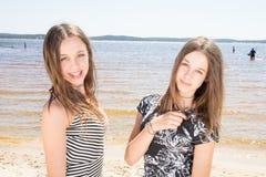 Deux jumelles de soeurs dans les filles d'adolescent de beauté de vacances de plage d'été Images stock