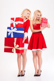 Deux jumelles de soeurs dans Santa costume les présents se tenants et s'ouvrants Images stock