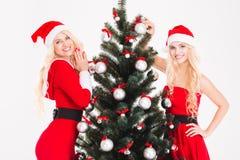 Deux jumelles de sourire de soeurs dans des robes et des chapeaux du père noël Images libres de droits