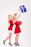 Deux jumelles espiègles de soeurs dans des robes du père noël ayant l'amusement Images libres de droits