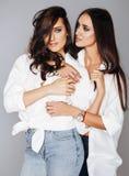 Deux jumelles pose émotive de soeurs, faisant le selfie de photo, ont habillé la même chemise blanche, coiffure diverse, maquilla Photos stock