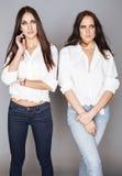 Deux jumelles pose de soeurs, faisant la photo, habillée Photo libre de droits
