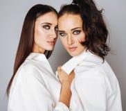 Deux jumelles pose de soeurs, faisant la photo, habillée Images stock