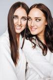 Deux jumelles pose de soeurs, faisant la photo, habillée Image stock