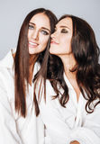 Deux jumelles pose de soeurs, faisant la photo, habillée Photos stock