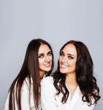 Deux jumelles pose de soeurs, faisant la photo, ont habillé la même chemise blanche Photographie stock libre de droits