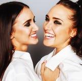 Deux jumelles pose de soeurs, faisant la photo, ont habillé la même chemise blanche Image stock