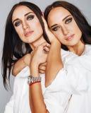 Deux jumelles pose de soeurs, faisant le selfie de photo, ont habillé la même chemise blanche, amis divers de coiffure Image libre de droits