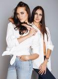 Deux jumelles pose de soeurs, faisant le selfie de photo, ont habillé la même chemise blanche, amis divers de coiffure Photographie stock libre de droits