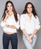 Deux jumelles pose de soeurs, faisant le selfie de photo, ont habillé la même chemise blanche, amis divers de coiffure Image stock