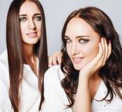 Deux jumelles pose de soeurs, faisant le selfie de photo, ont habillé la même chemise blanche, amis divers de coiffure Photographie stock