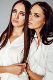 Deux jumelles pose de soeurs, faisant le selfie de photo, ont habillé la même chemise blanche, amis divers de coiffure Photo libre de droits
