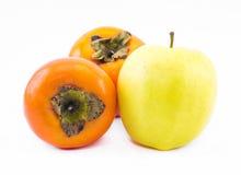 Deux kakis oranges et une pomme jaune sur un fond blanc Photos stock