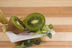 Deux kiwis découpés en tranches d'un plat blanc Photo libre de droits