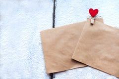 Deux l'enveloppe de l'agrafe de papier d'emballage sous forme de coeur dans la neige le jour du ` s de Valentine, attitudes du `  Image stock