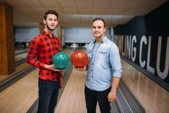 Deux lanceurs masculins pose sur la ruelle avec des boules sur des mains image libre de droits