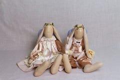 Deux lapins de jouet, un ange, dans des équipements beiges se reposent sur le fond Photo libre de droits