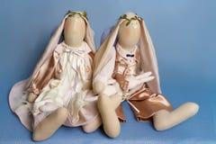 Deux lapins de jouet, un ange, dans des équipements beiges se reposent sur le fond Photographie stock