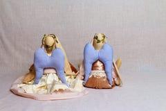 Deux lapins de jouet, un ange, dans des équipements beiges se reposent sur le fond Images libres de droits