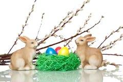 Deux lapins de Pâques mignons s'approchent de l'emboîtement d'oeufs de pâques Photographie stock