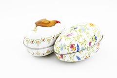Deux lapins en céramique blancs de Pâques et deux oeufs colorés de bidon photographie stock