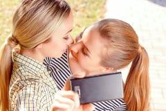 Deux lesbiennes faisant le selfie en parc Images stock