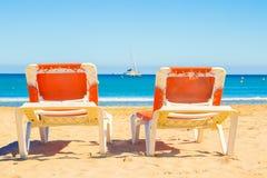 Deux lits du soleil sur la plage sont tournés vers la mer images stock