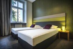 Deux lits simples dans la chambre d'hôtel verte Images stock