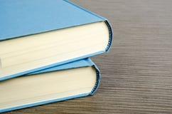 Deux livres bleus sur une table avec la texture en bois Image libre de droits