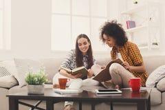 Deux livres de lecture femelles d'amis à la maison Images stock