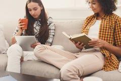 Deux livres de lecture femelles d'amis à la maison Photographie stock libre de droits