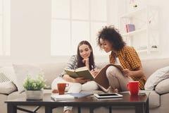 Deux livres de lecture femelles d'amis à la maison Photos libres de droits