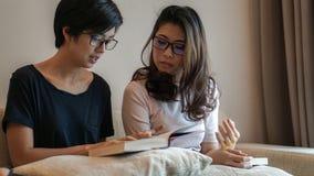 Deux livres et discussions de lecture asiatiques d'amies de femme sur le passe-temps Photographie stock libre de droits