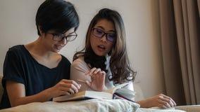 Deux livres et discussions de lecture asiatiques d'amies de femme sur le passe-temps Photographie stock
