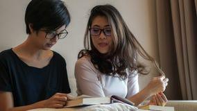 Deux livres et discussions de lecture asiatiques d'amies de femme sur le passe-temps Photo libre de droits