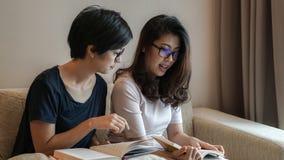 Deux livres et discussions de lecture asiatiques d'amies de femme sur le passe-temps Photos stock
