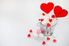 Deux lucettes en forme de coeur dans le petit seau avec des bonbons sur le blanc Image libre de droits