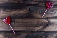 Deux lucettes en forme de coeur sur la table en bois Photographie stock libre de droits