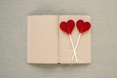 Deux lucettes en forme de coeur sur un vieux journal intime Photos stock