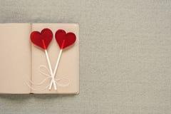 Deux lucettes en forme de coeur sur un vieux journal intime Image libre de droits